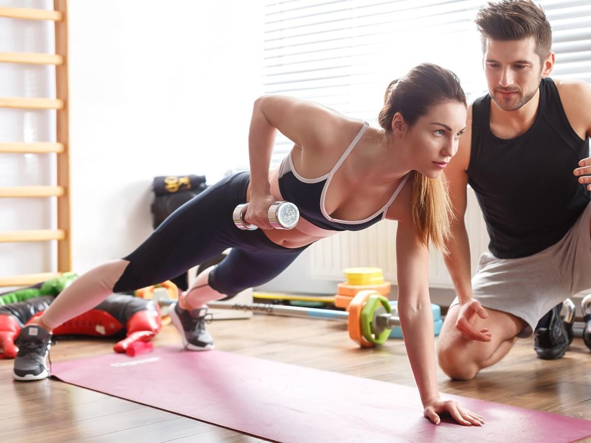 Trener personalny ćwiczy z kobietą.