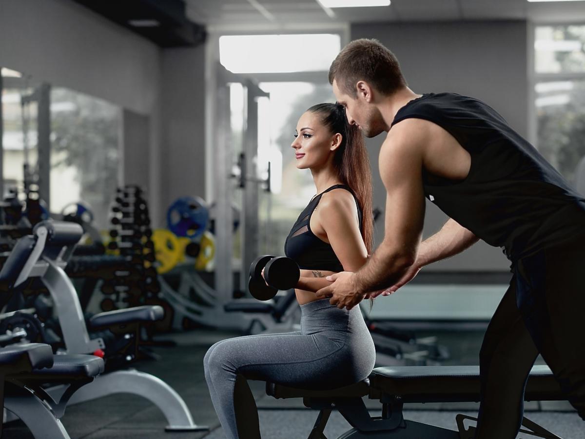 trener pomagający ćwiczyć kobiecie na siłowni
