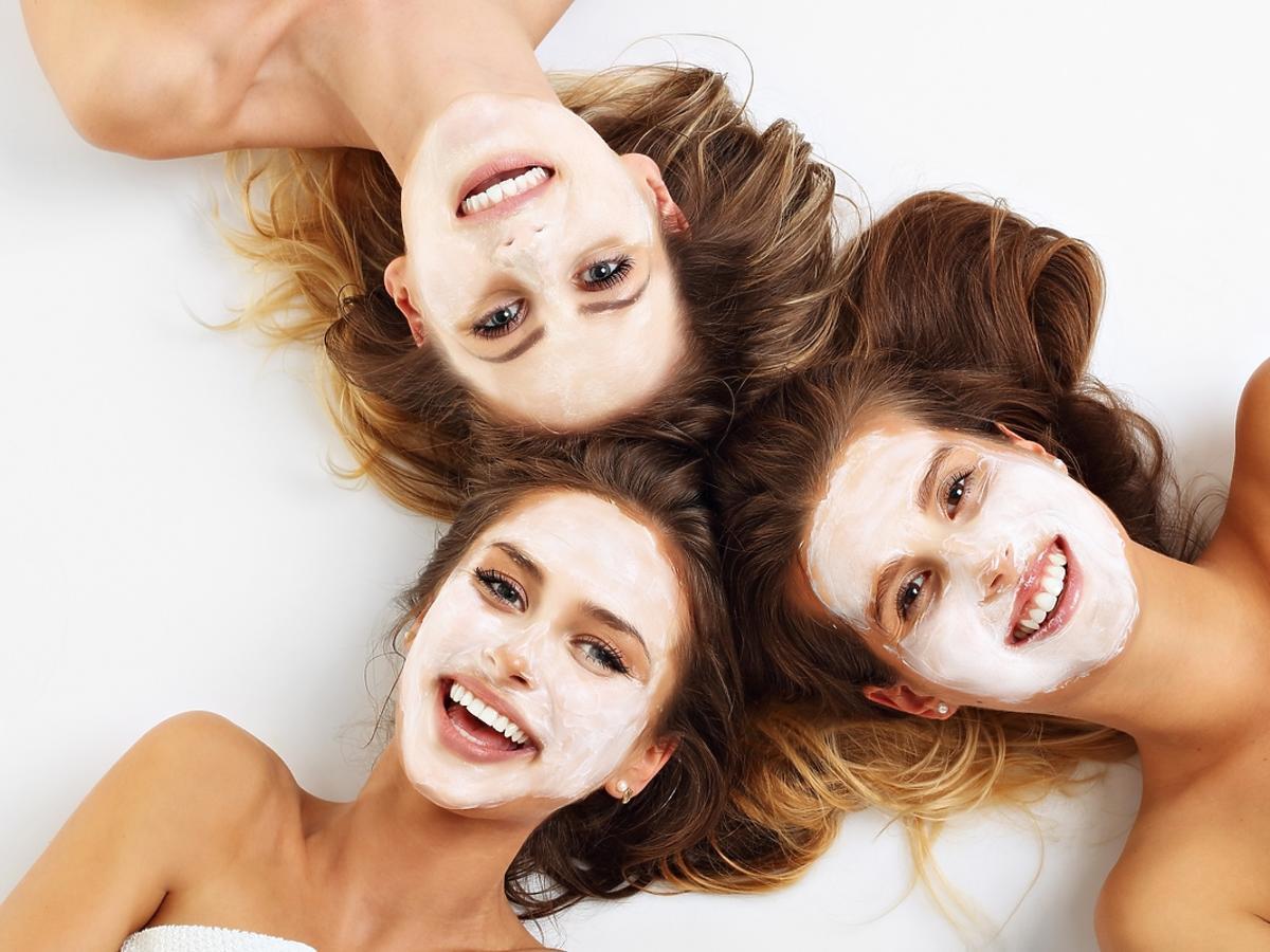 Trzy kobiety nałożyły na twarz maseczki przeciwtrądzikowe.
