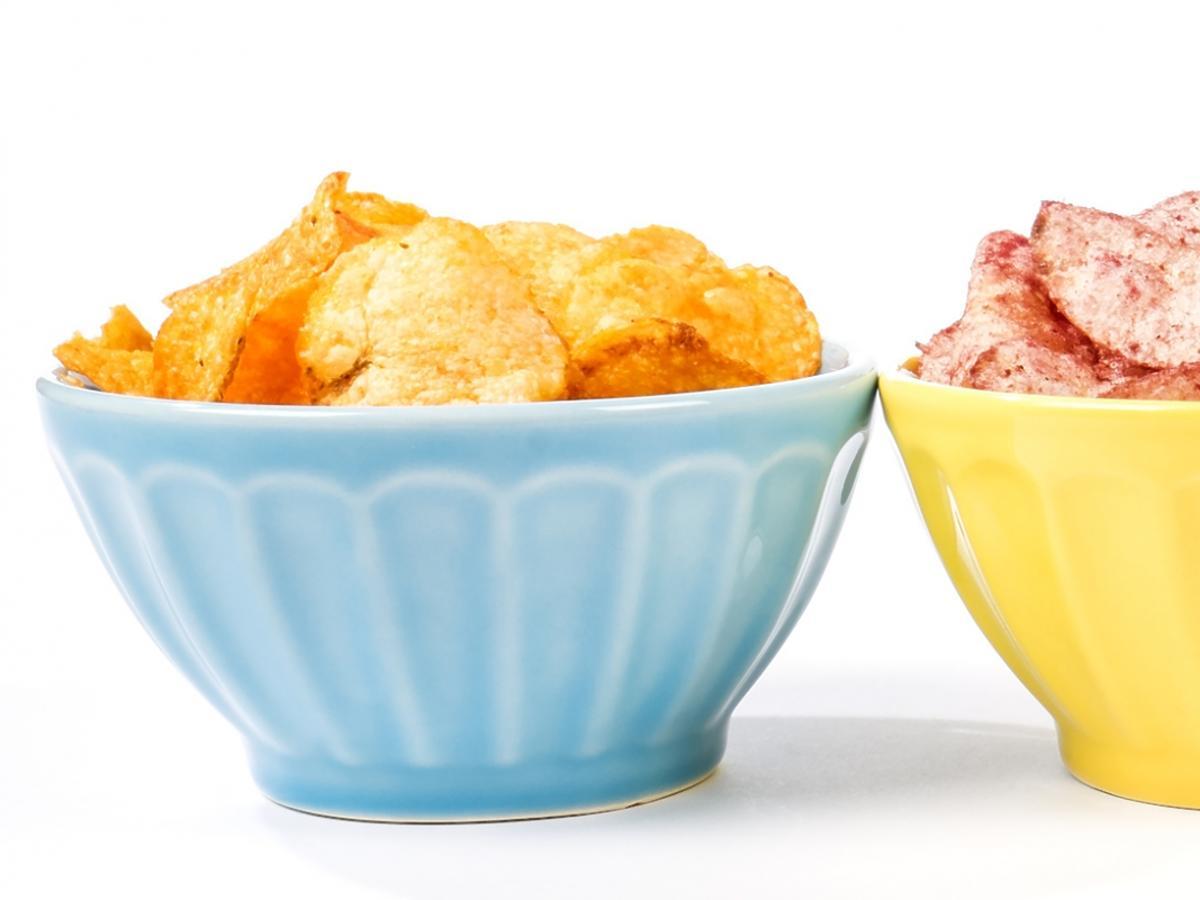 trzy kolorowe miseczki z czipsami w różnych smakach