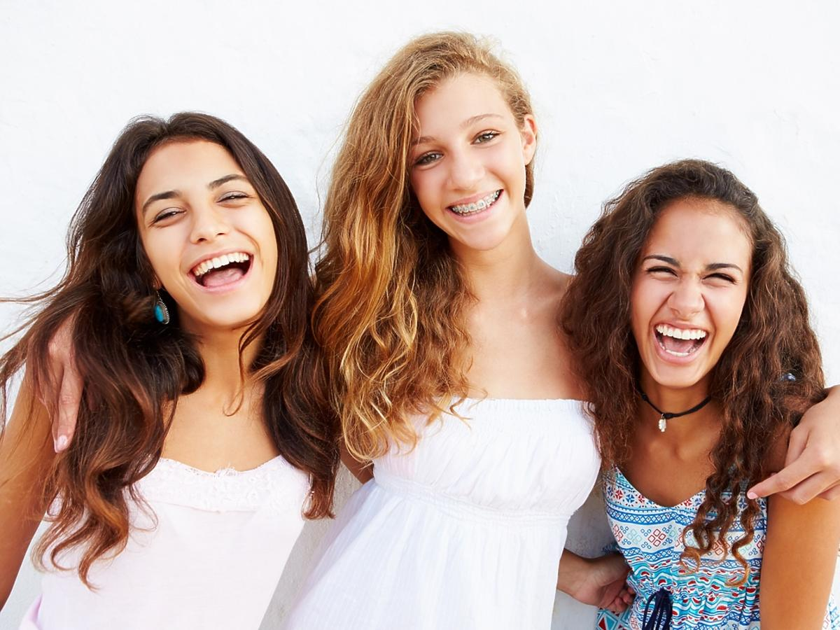 Trzy nastolatki uśmiechają się do obiektywu aparatu.