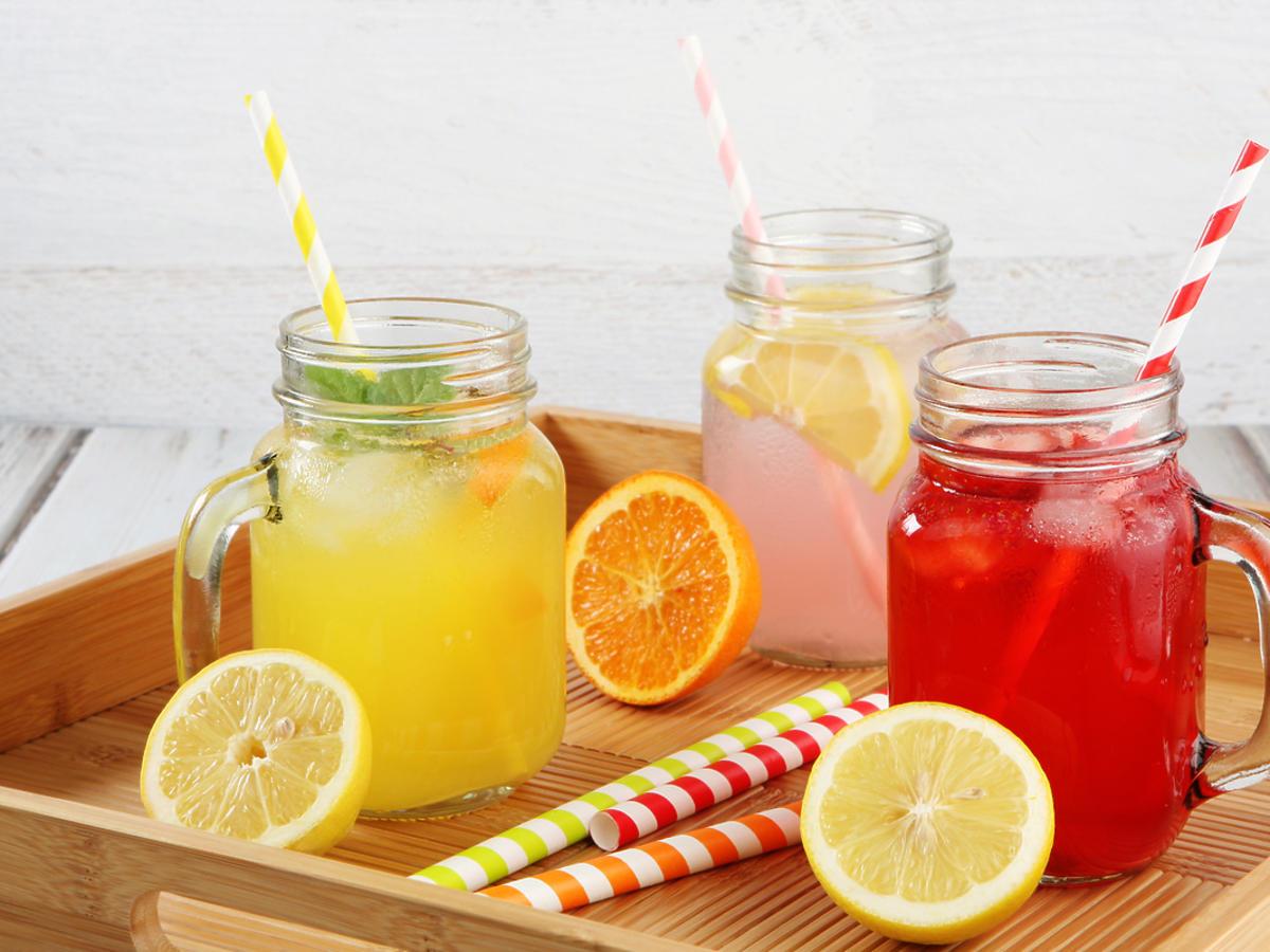 Trzy owocowe lemoniady w wysokich szklankach