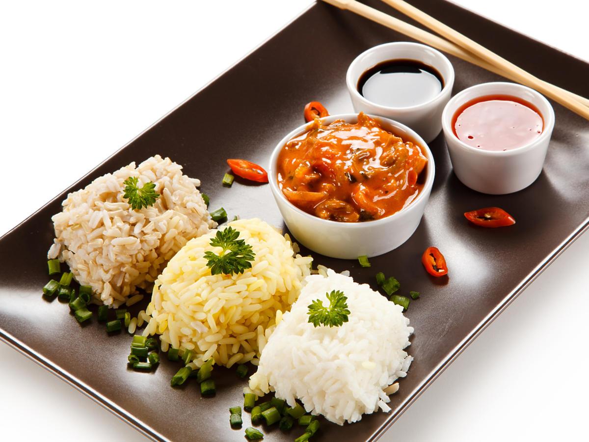 Trzy rodzaje ryżu podane z sosem na talerzu.