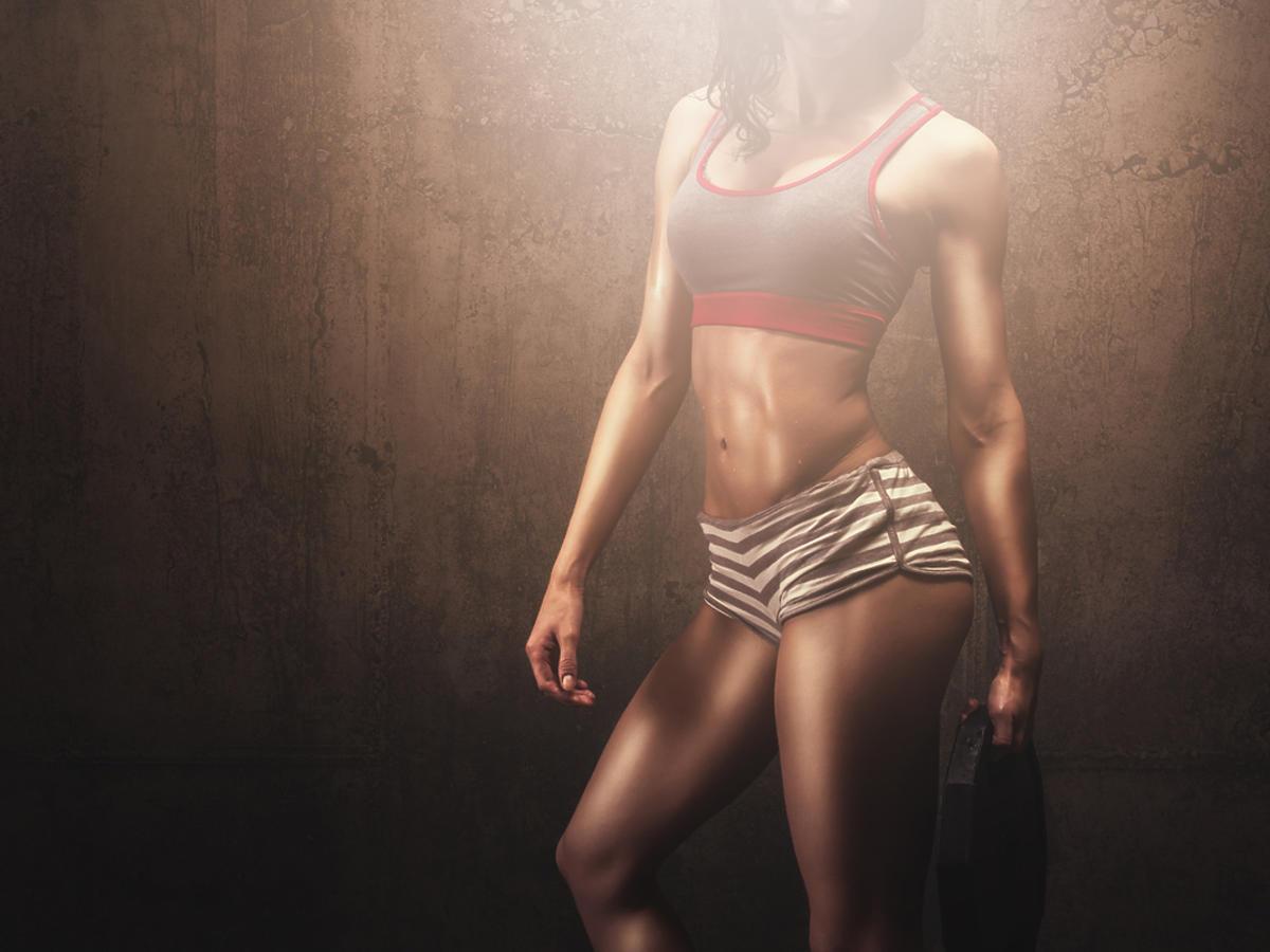 Umięśniona kobieta w stroju sportowym podczas treningu z ciężarkami