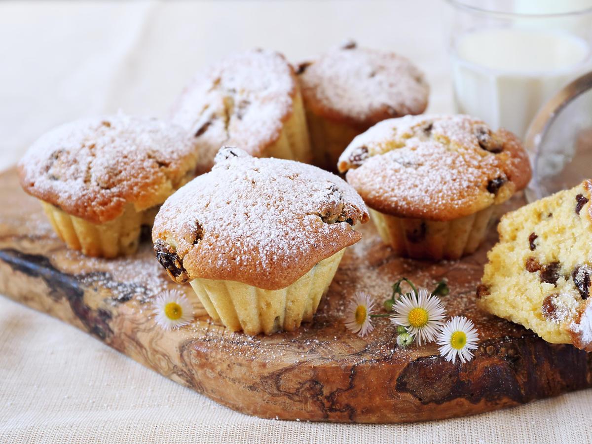 Upieczone muffinki posypane cukrem pudrem i przybrane stokrotkami