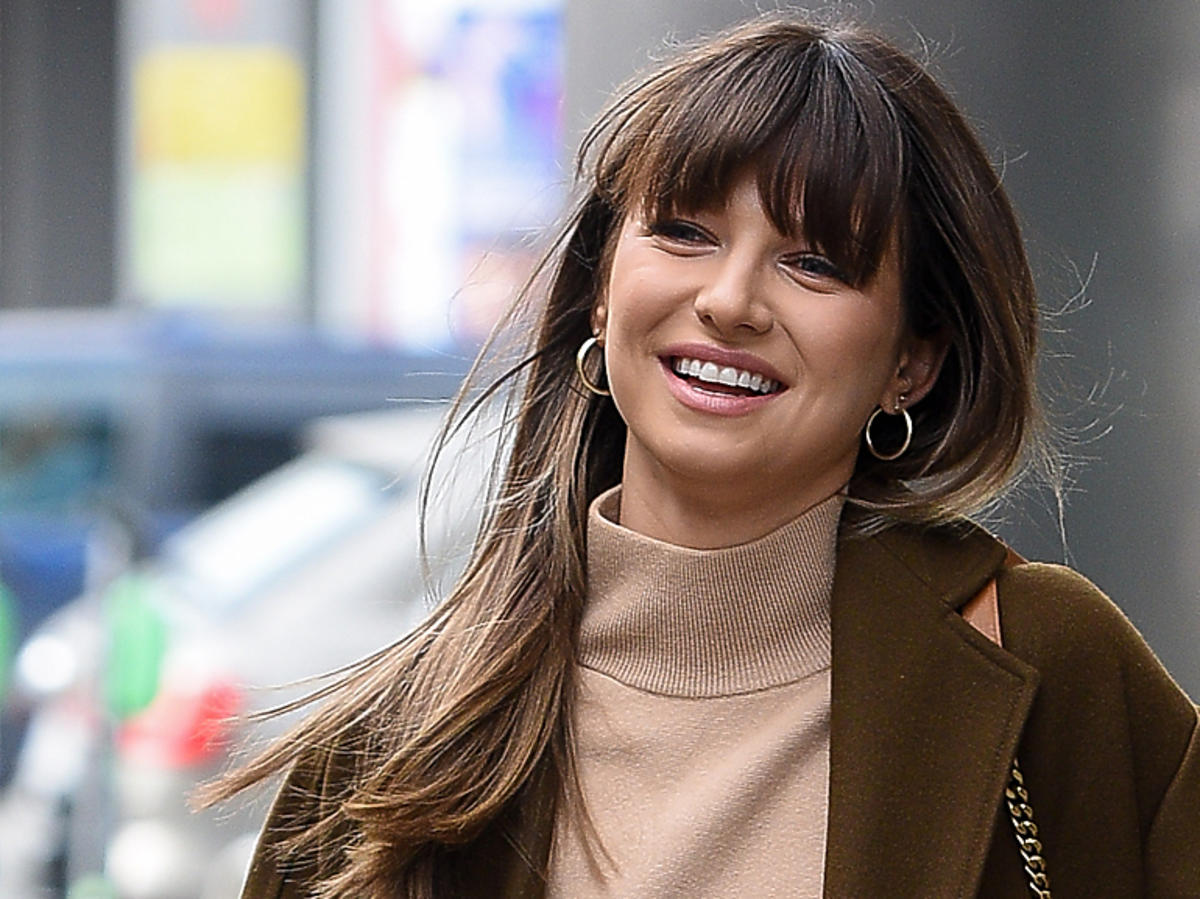 Uśmiechnięta Anna Lewandowska w brązowym płaszczu
