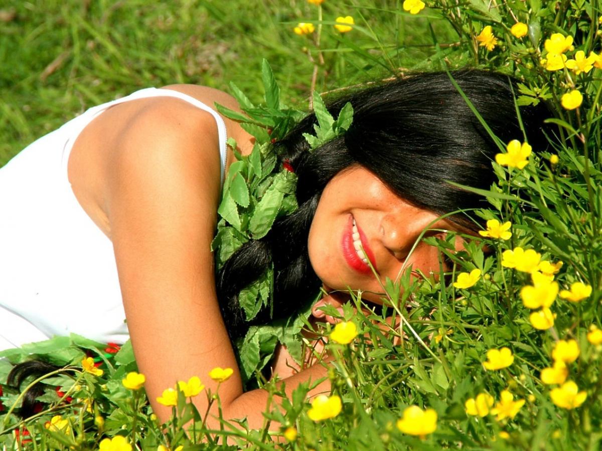 Uśmiechnięta brunetka leży na trawie.