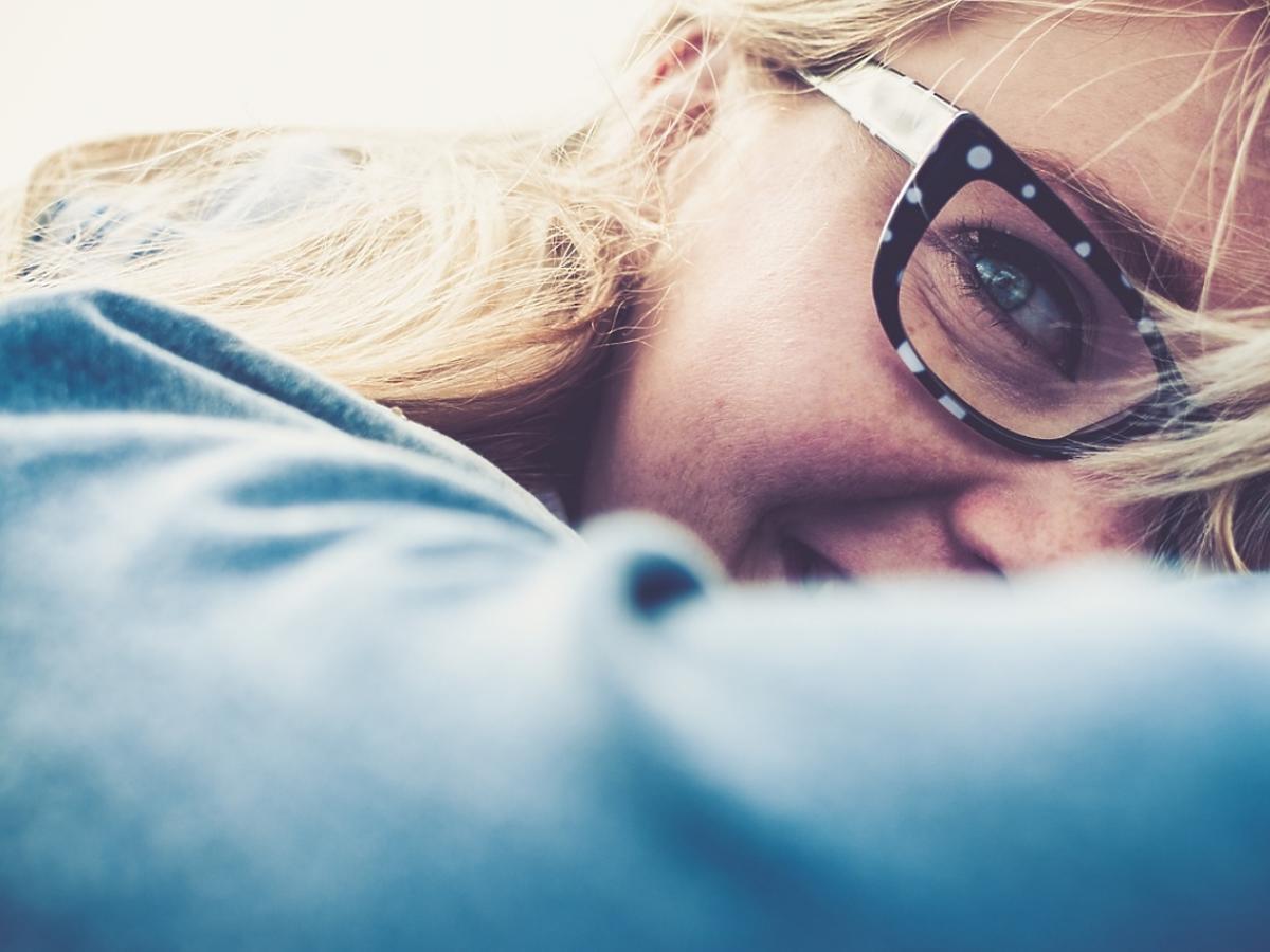 uśmiechnięta dziewczyna w okularach