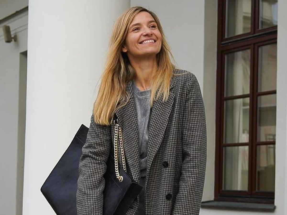 Uśmiechnięta Joanna Koroniewska w szarym płaszczu