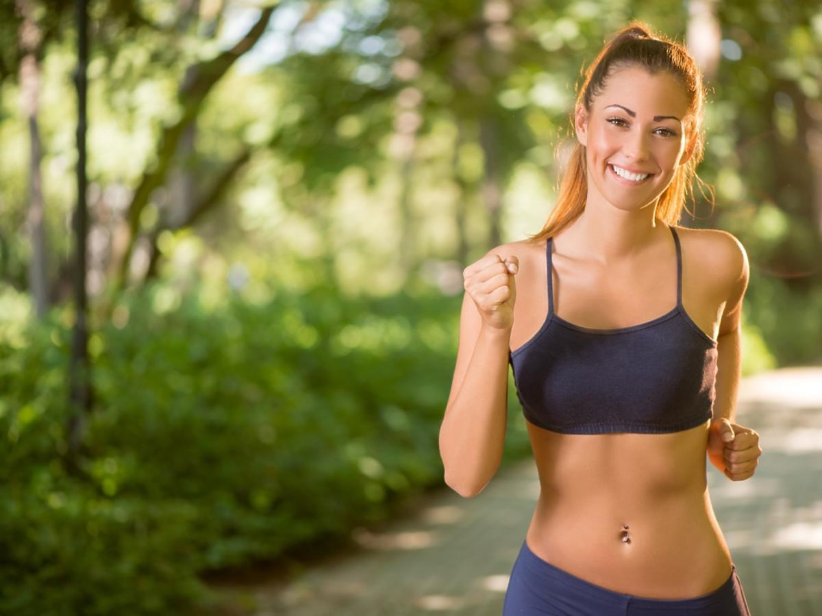 uśmiechnięta kobieta biega po lesie