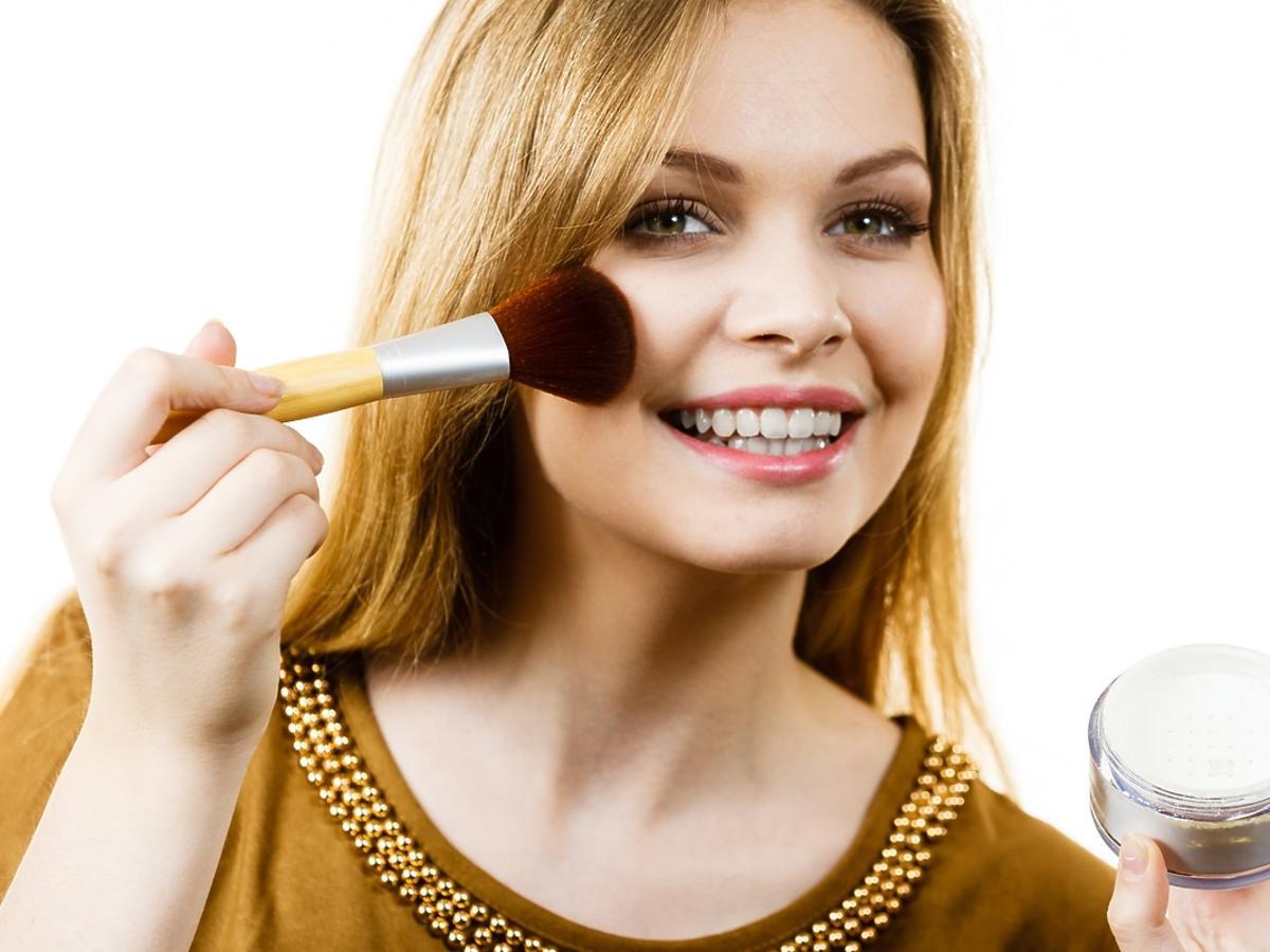 uśmiechnięta kobieta malująca twarz pędzlem do pudru z pudrem ryżowym