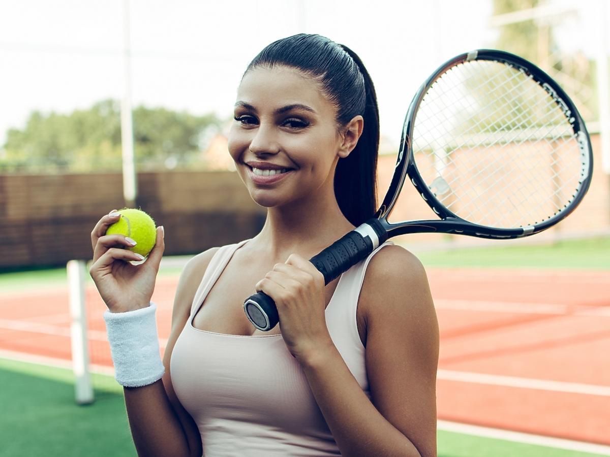 uśmiechnięta kobieta na korcie tenisowym z rakietą do tenisa w dłoni
