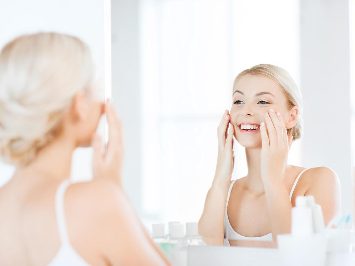 uśmiechnięta kobieta przed lustrem