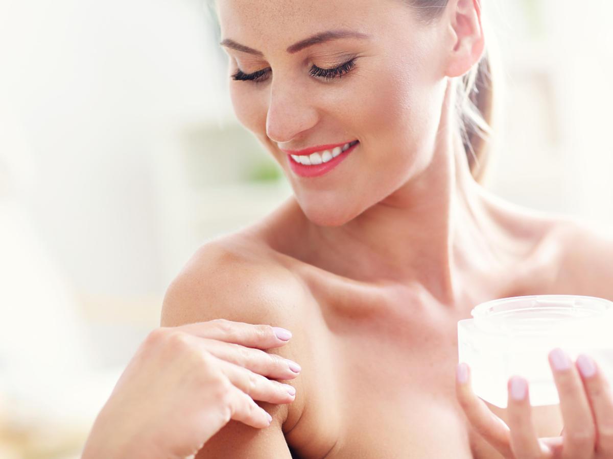 uśmiechnięta kobieta smaruje ramię kremem