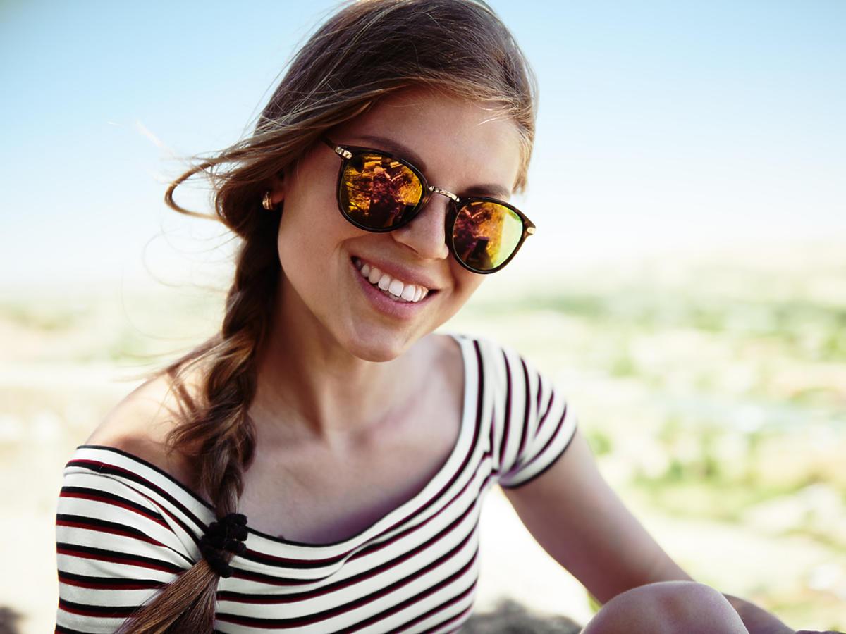 uśmiechnięta kobieta w okularach przeciwsłonecznych