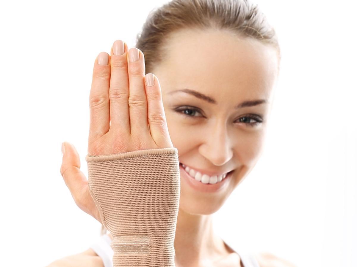 uśmiechnięta kobieta z założonym na rękę stabilizatorem sportowym