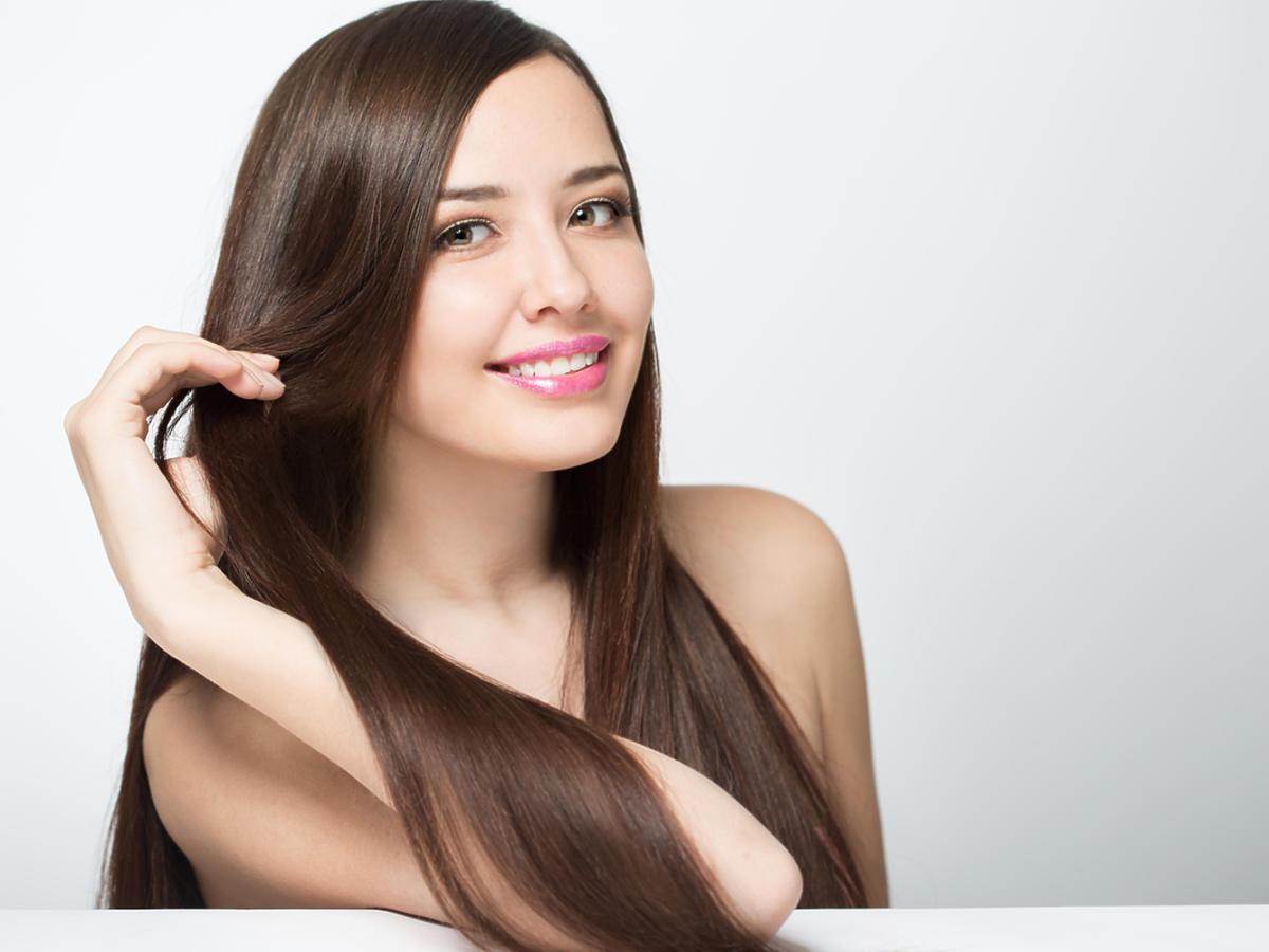 uśmiechnięta młoda kobieta z długimi prostymi włosami