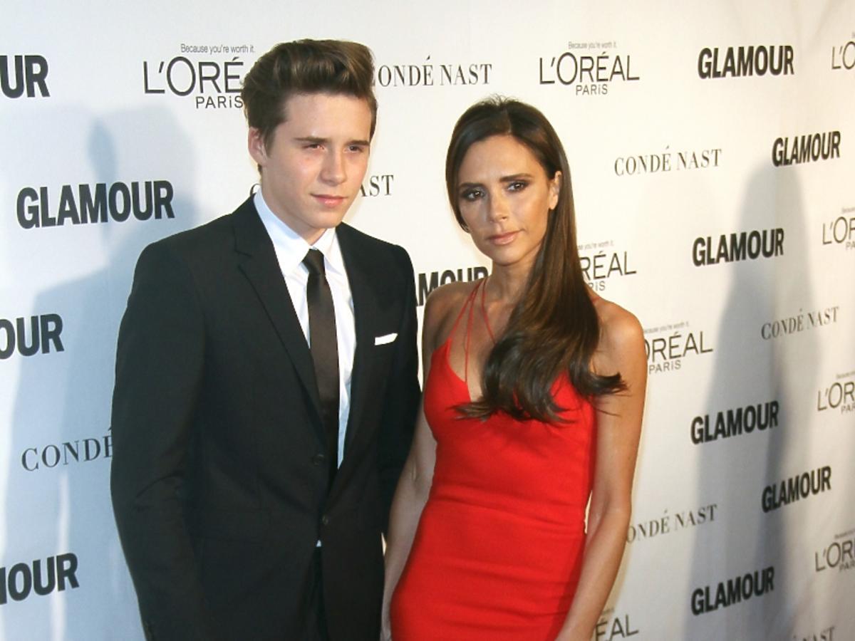 Victoria Beckham w długiej, czerownej sukni. Brooklyn Beckham w garniturze