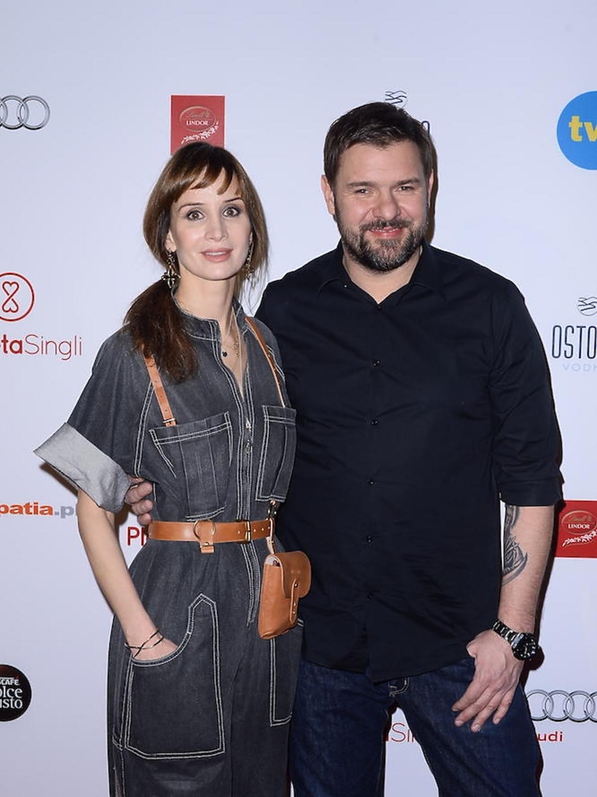 Viola Kołakowska w czarnym kobinezonie i Tomasz Karolak w czarnej koszuli na ściance