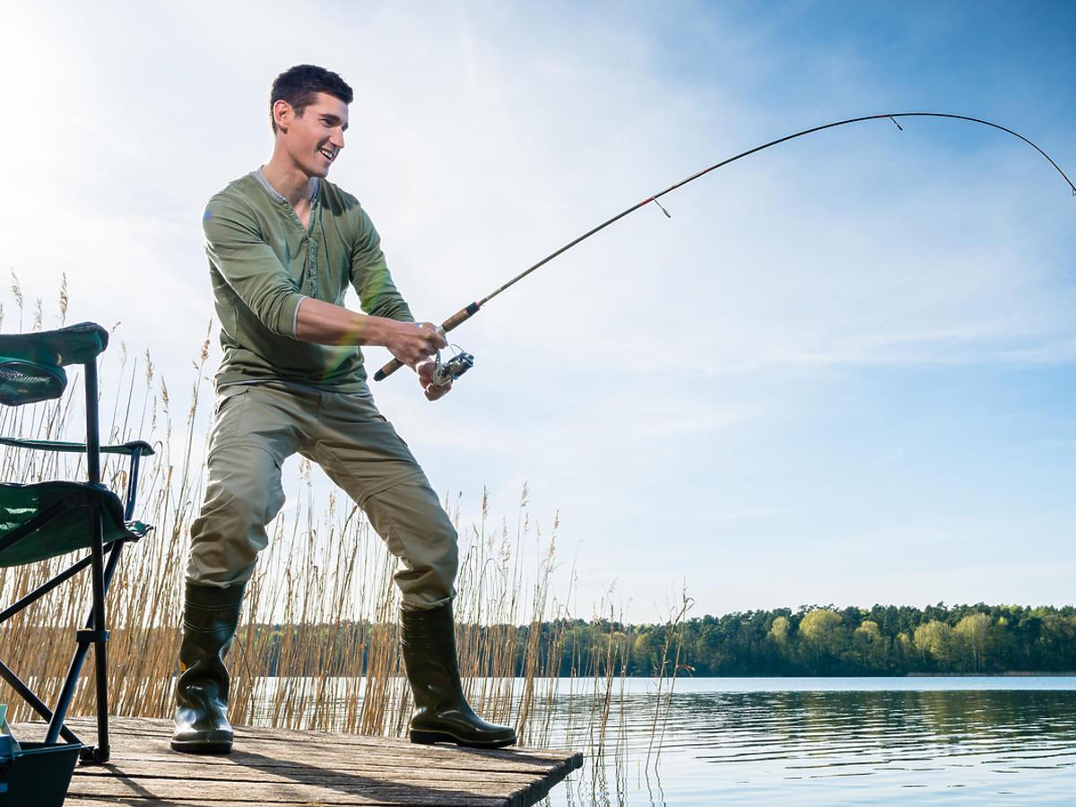 Wędkarz stoi na pomoście i łowi ryby