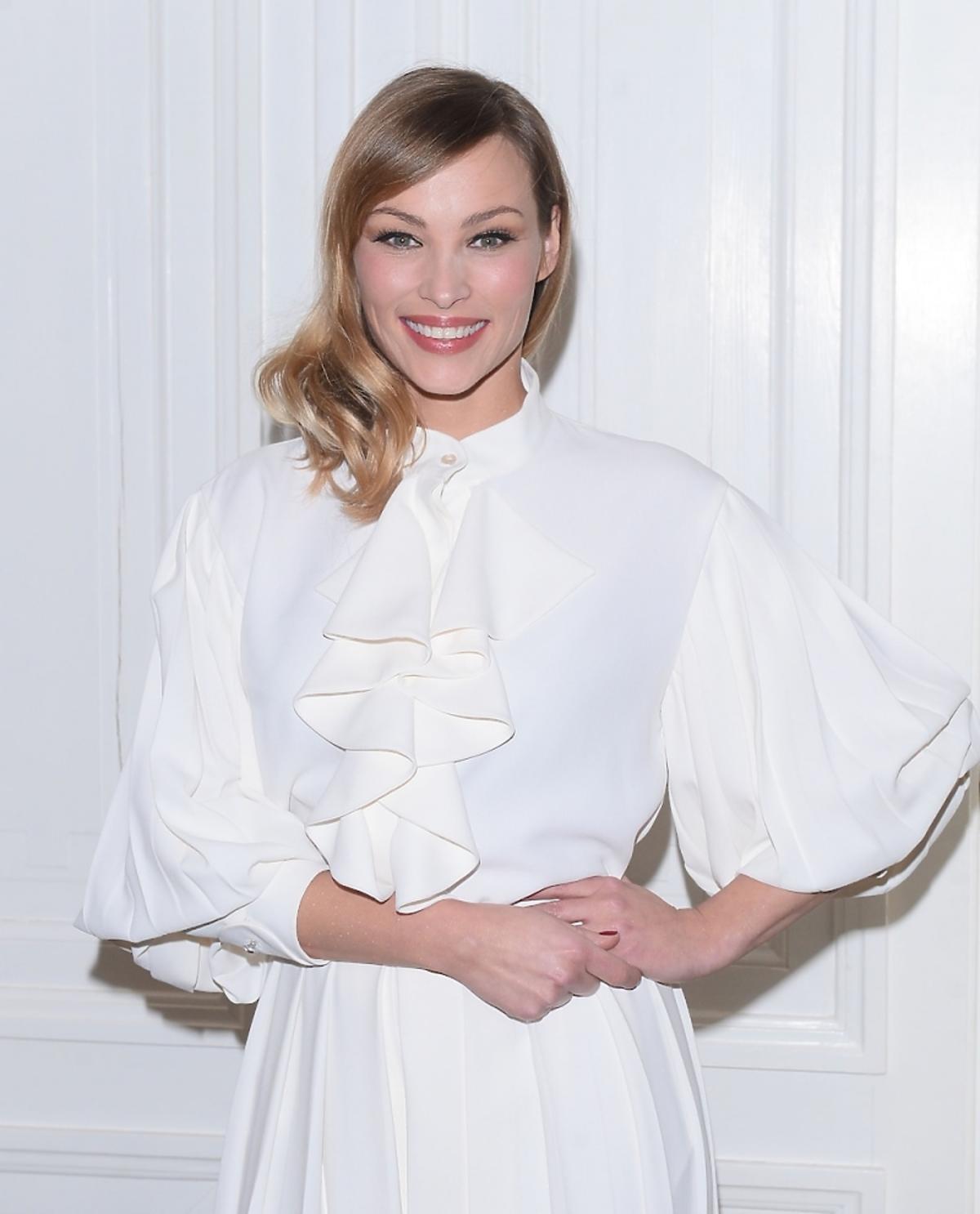 Weronika Książkiewicz w białej sukni z szerokimi rękawami i kokardą