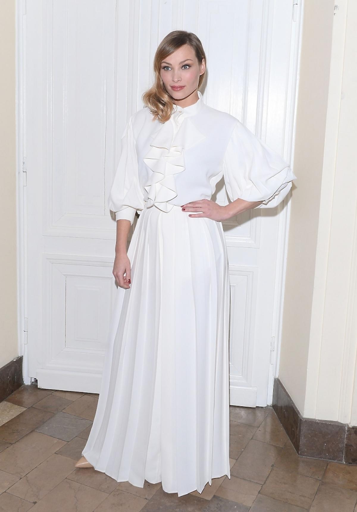 Weronika Książkiewicz w długiej białej sukni z szerokimi rękawami i kokardą