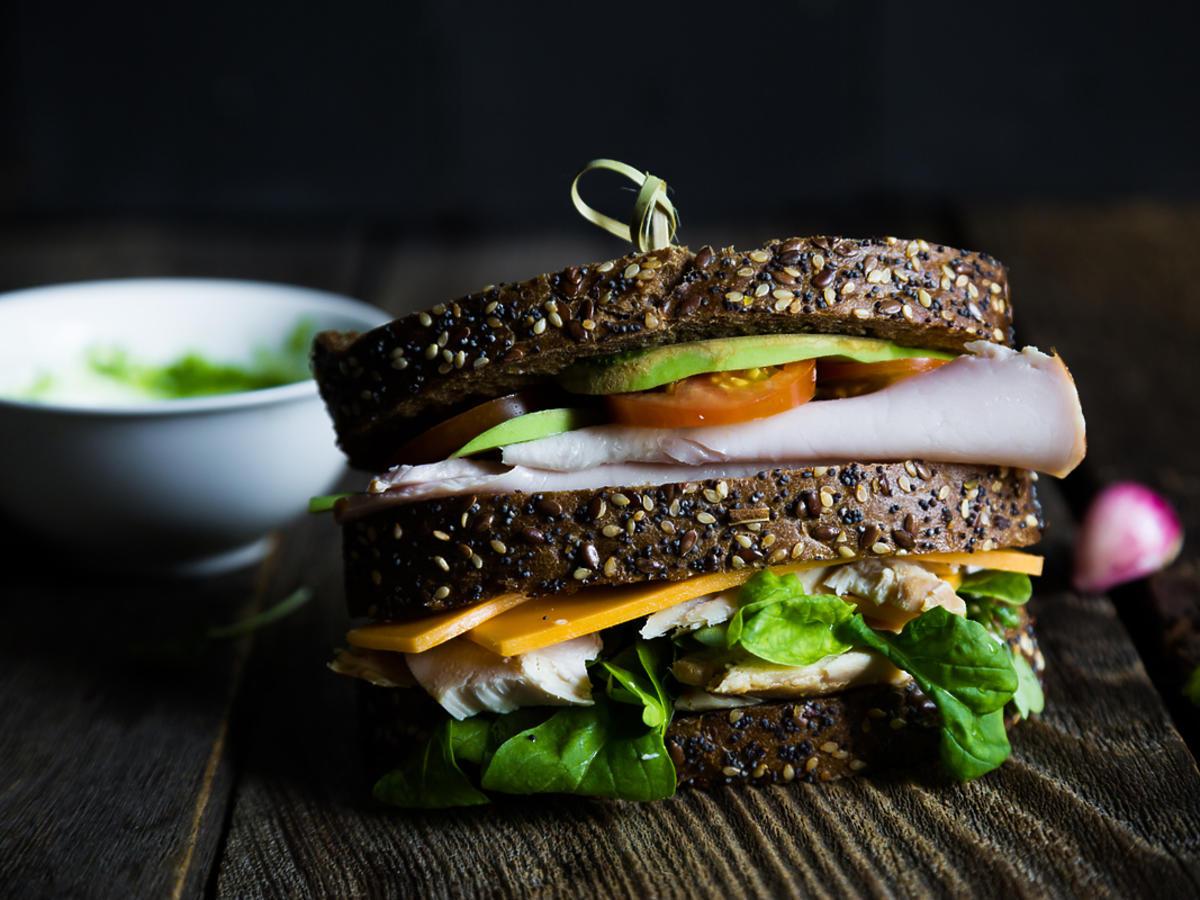Wielka kanapka z kurczakiem, warzywami i ciemnym chlebem.