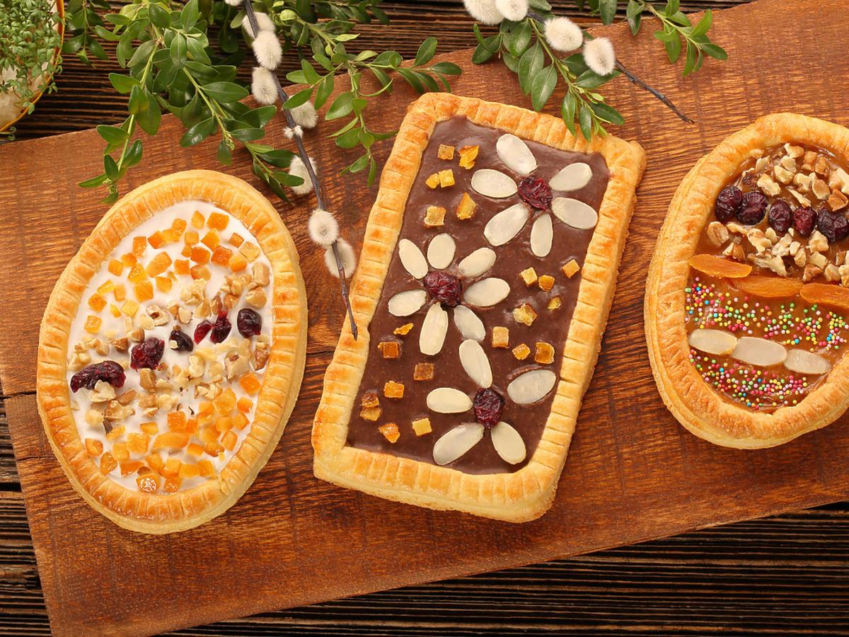 Wielkanocny mazurek polany gęstą czekoladą i posypany orzechami.