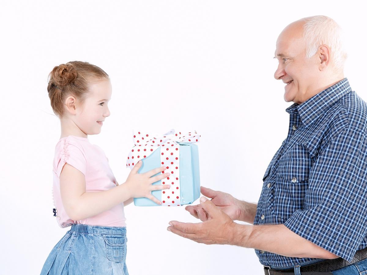 wnuczka wręczająca prezent dziadkowi