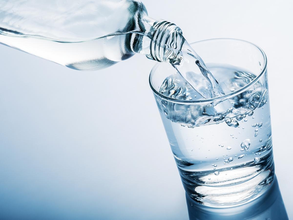 Woda leje się z butelki do szklanki