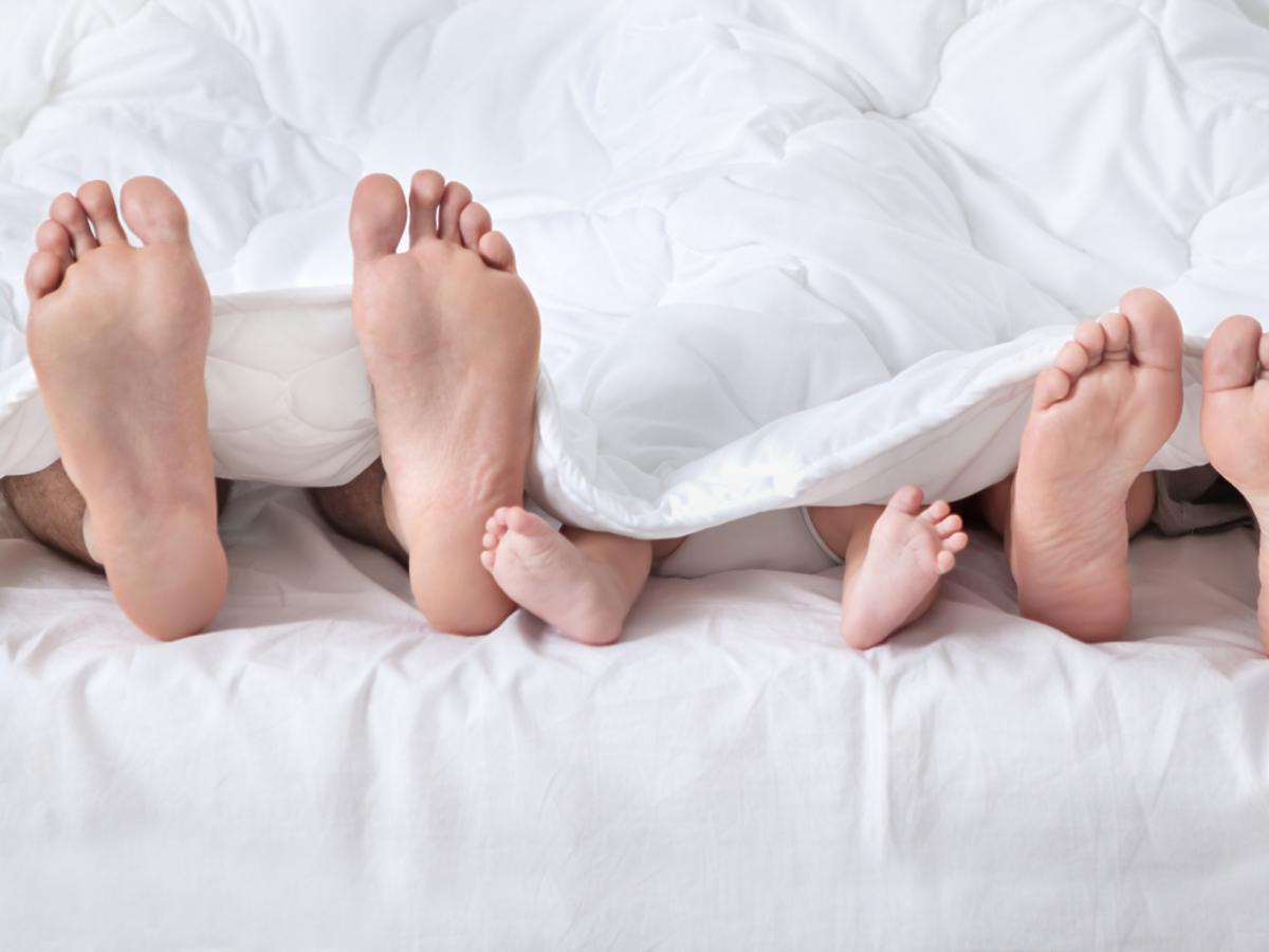 wystające spod kołdry stopy dziecka, mamy i taty