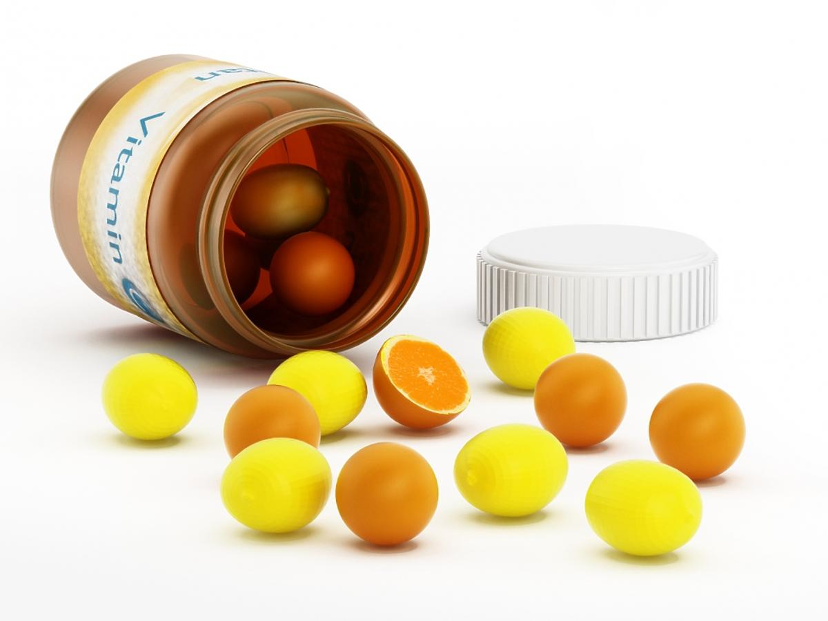 z buteleczki na witaminę c wysypują się pomarańcze i cytryny