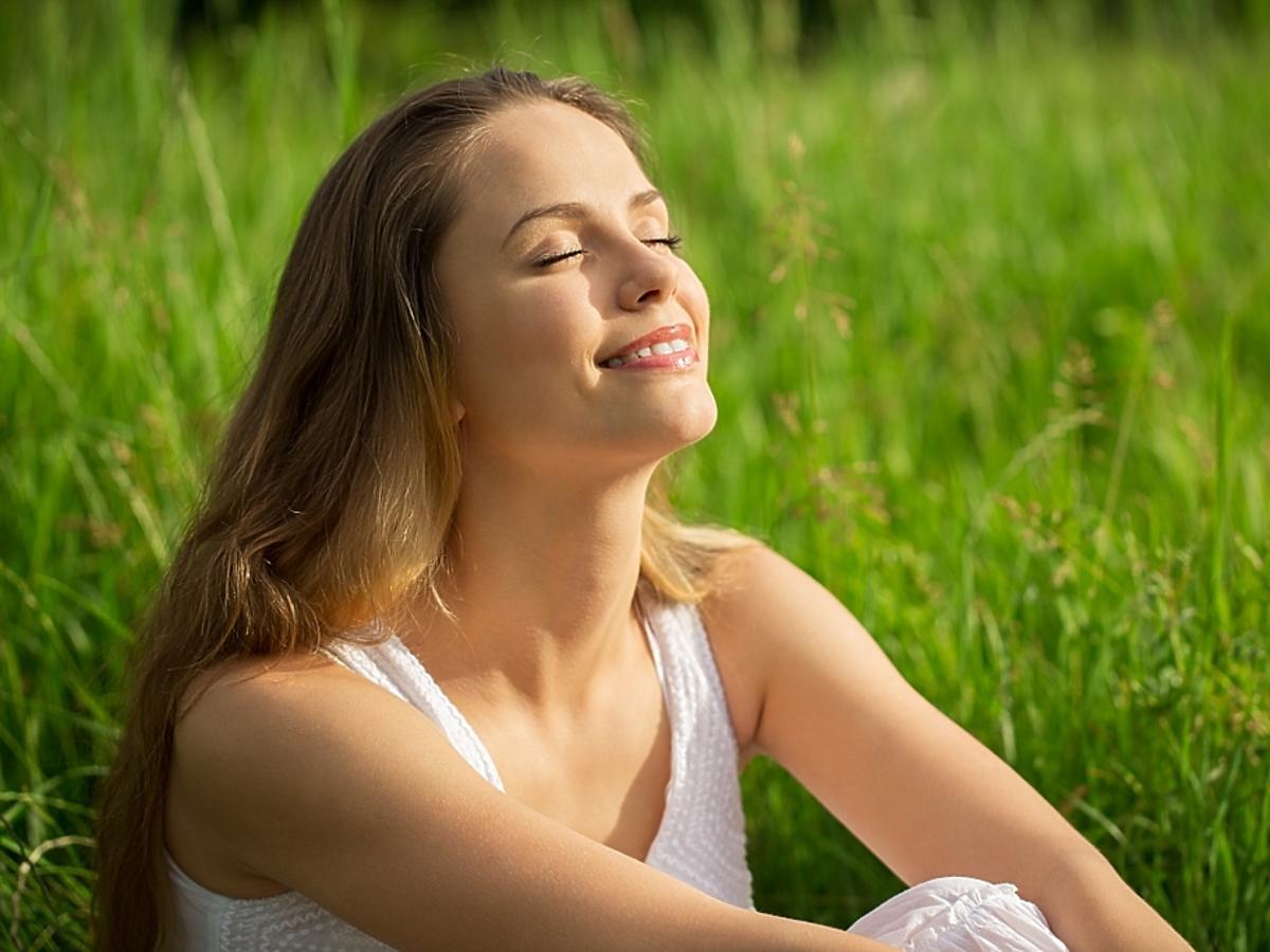 Zadowolona kobieta siedzi na łące