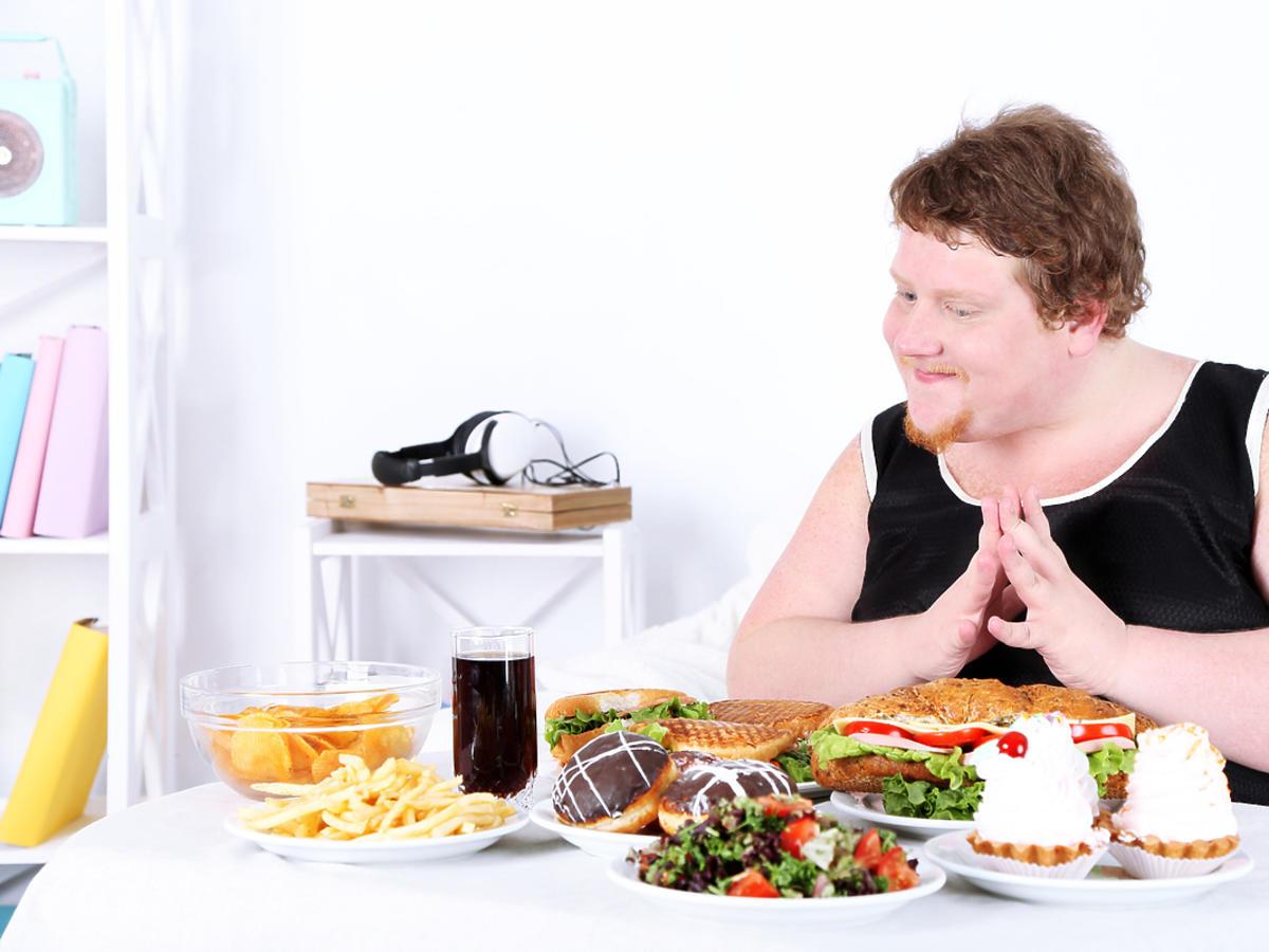 Zadowolony mężczyzna siedzący przy stole pełnym jedzenia.