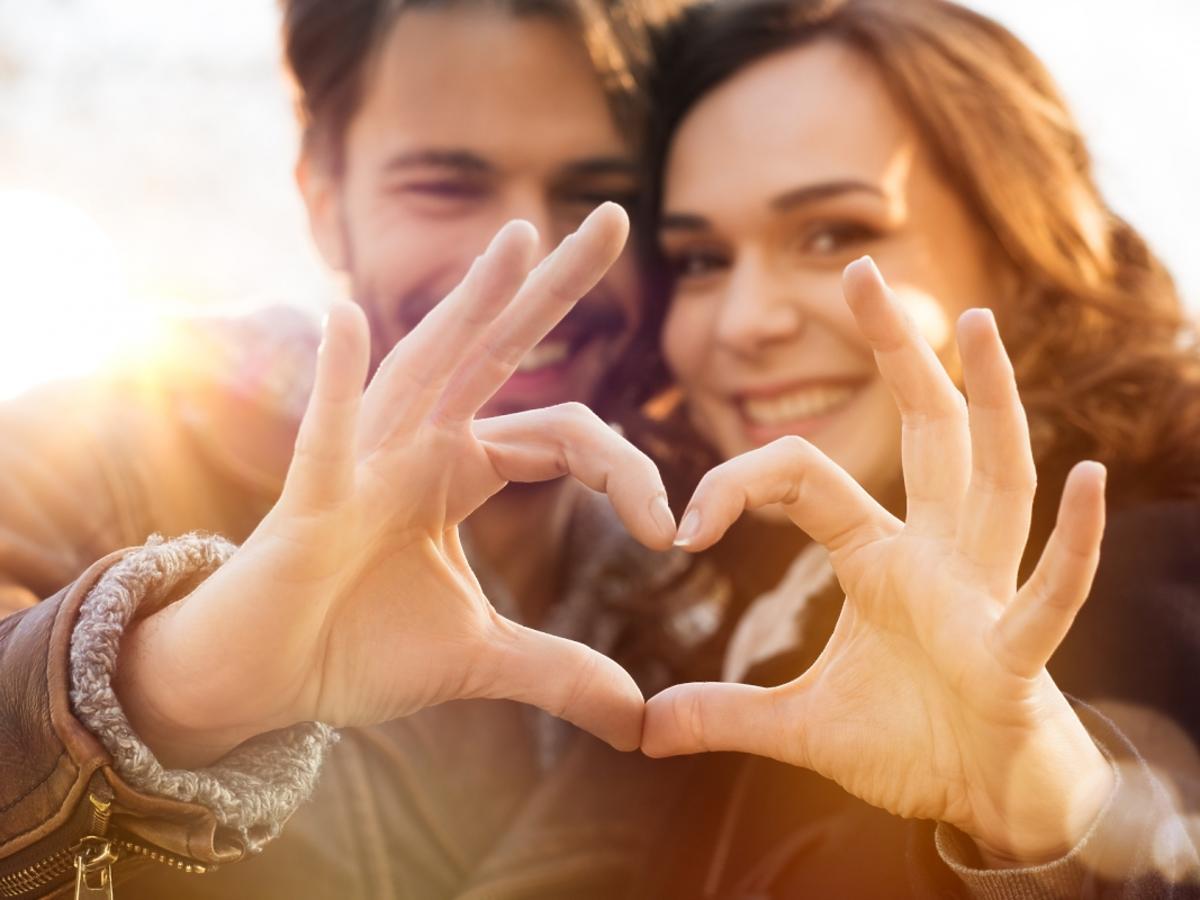 Zakochana para układa serce z dłoni