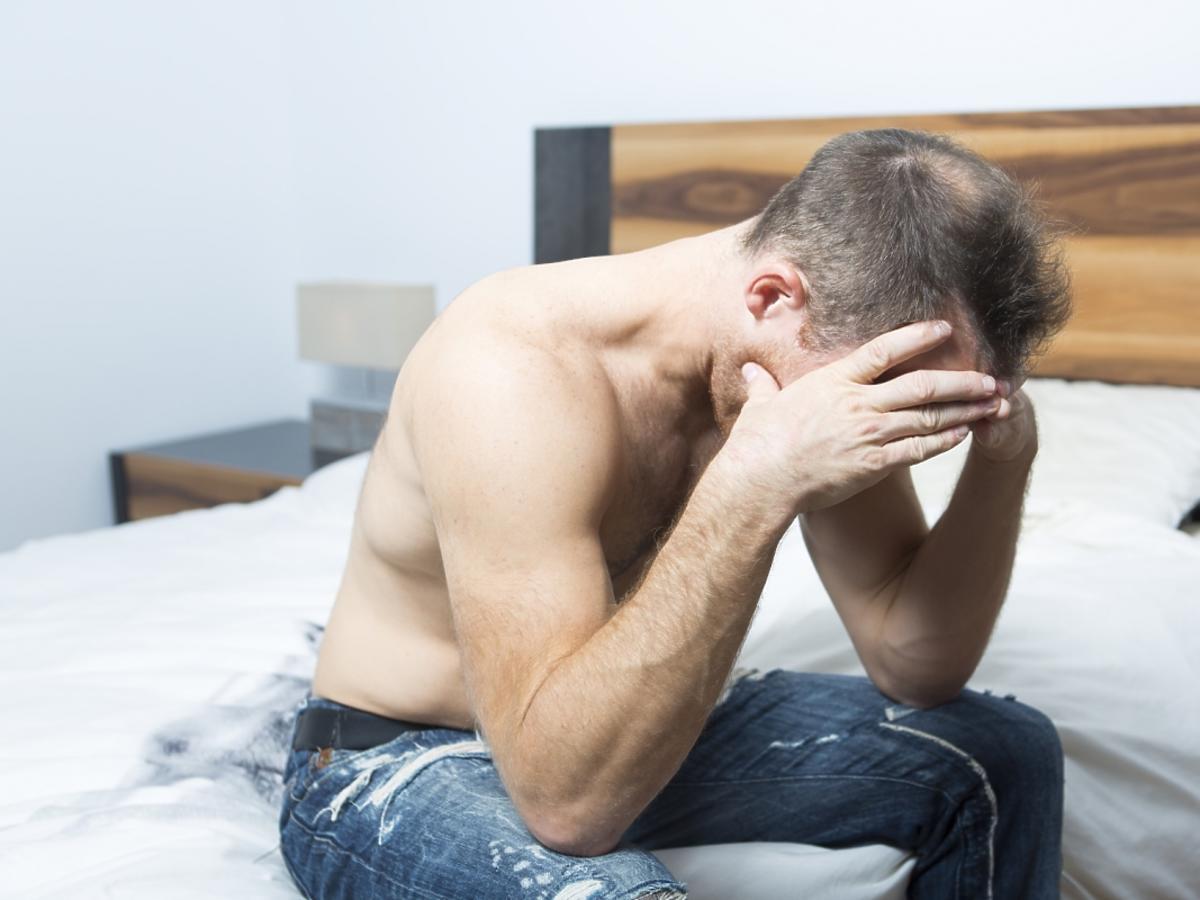 Załamany mężczyzna siedzi na łóżku