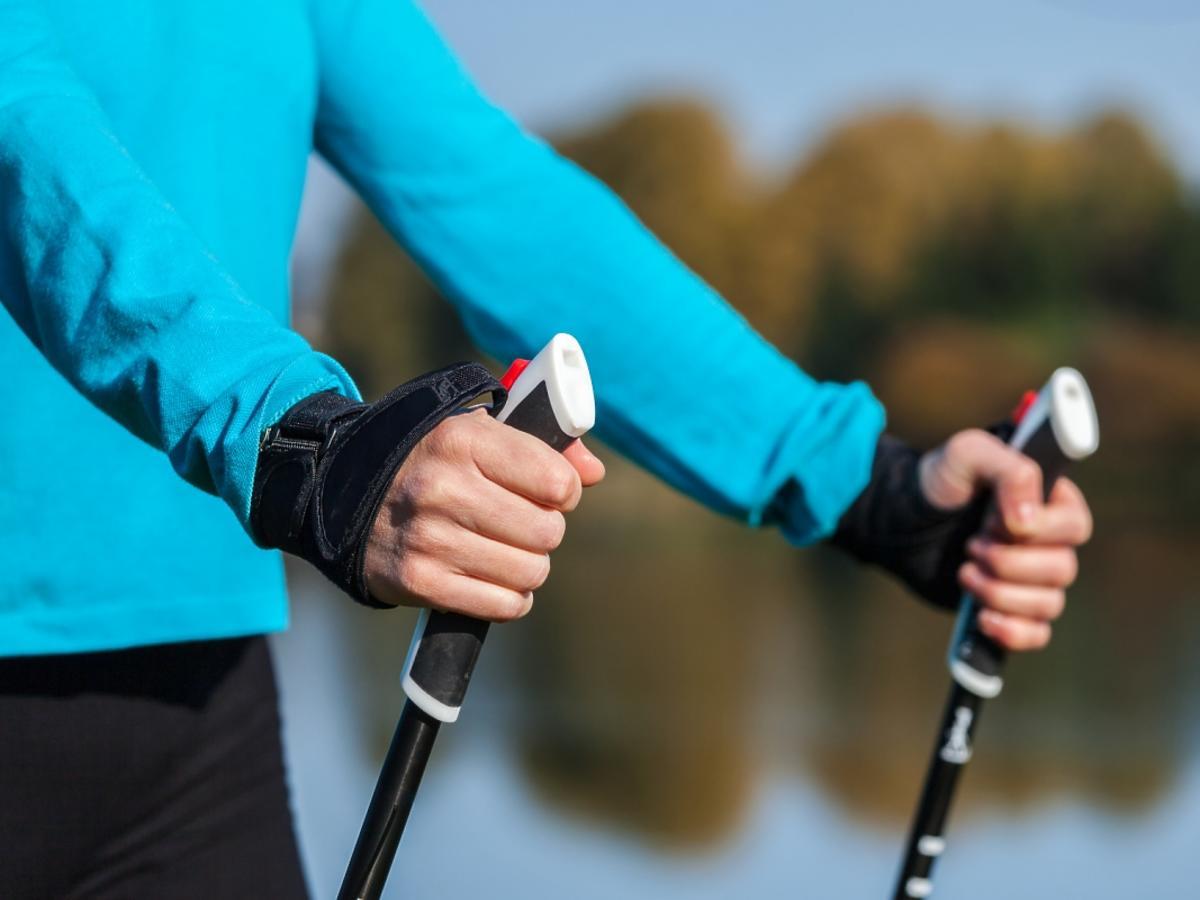 Zbliżenie na kobietę trzymającą kijki do nordic walking