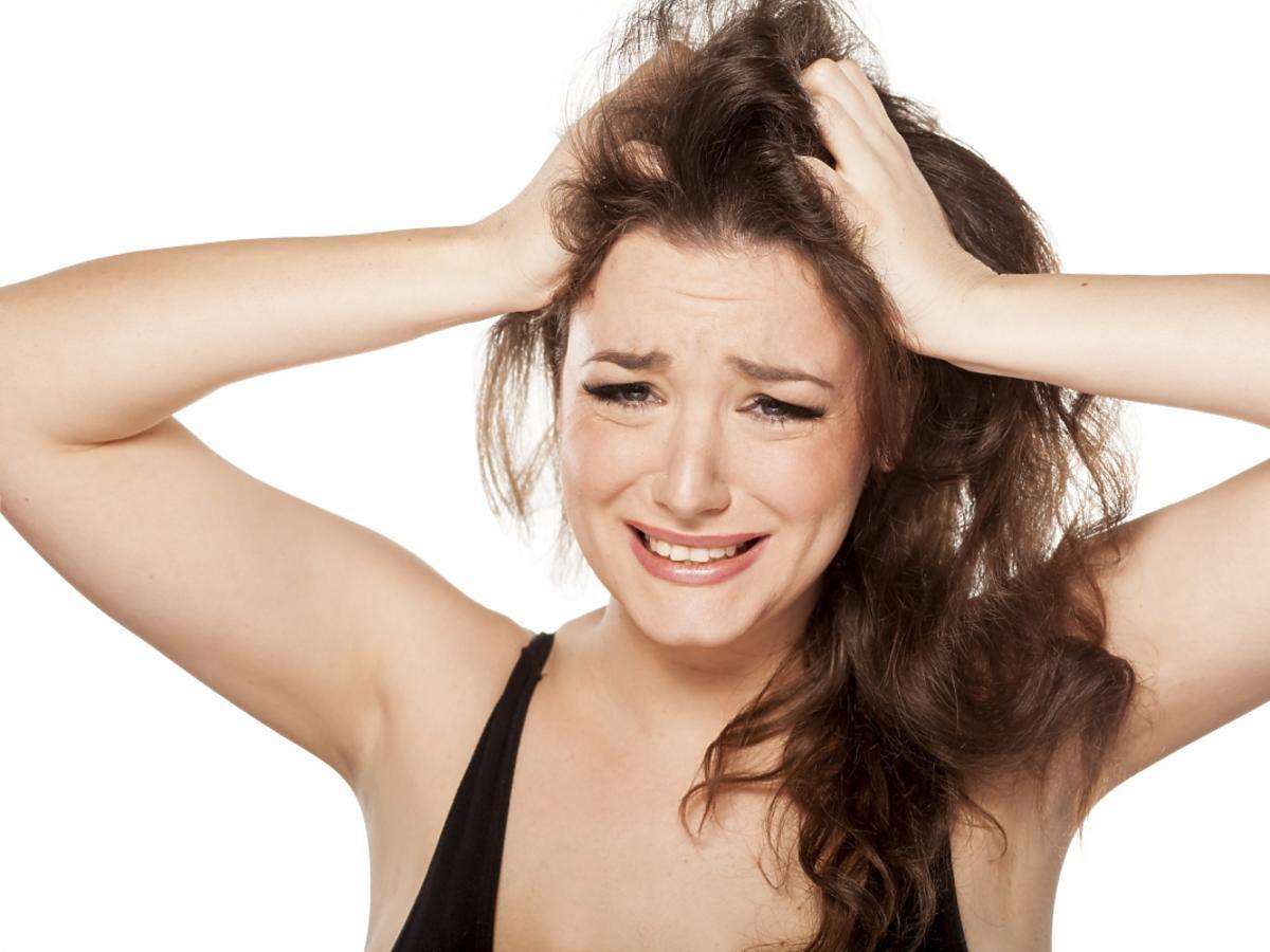 Zdenerwowana kobieta trzyma się za głowę.