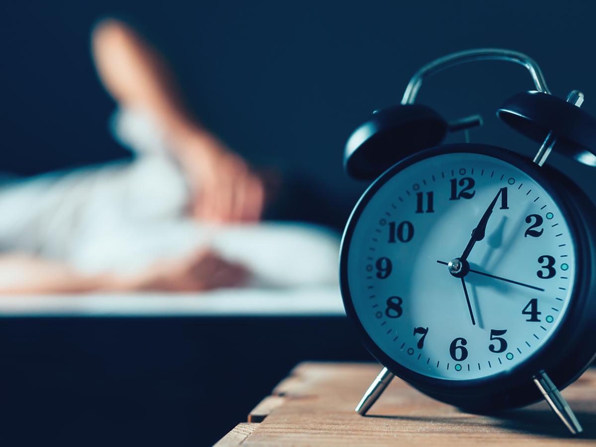 zegarek i kobieta siedząca na łóżku w tle