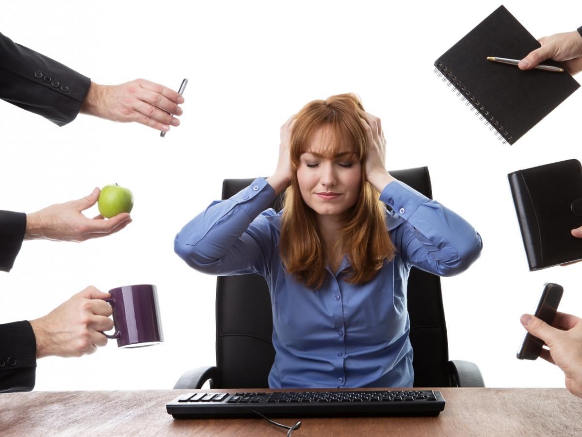zestresowana kobieta trzymająca się za głowę, w jej kierunku wyciągają się dłonie z różnymi przedmiotami