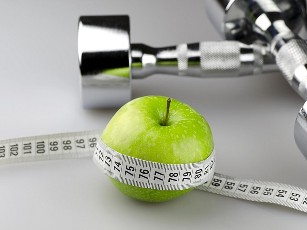 zielone jabłko i ciężarki do ćwiczeń