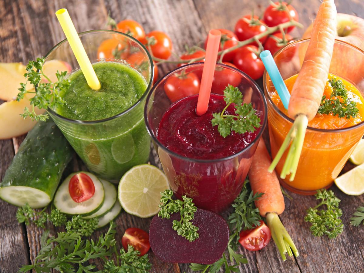 zielony, czerwony i pomarańczowy koktajl warzywny w szklankach. Obok świeże warzywa.