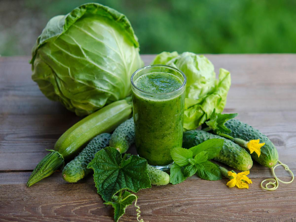 Zielony koktajl z cukinii z szklance, otoczony innymi świeżymi warzywami (cukinia, kapusta)