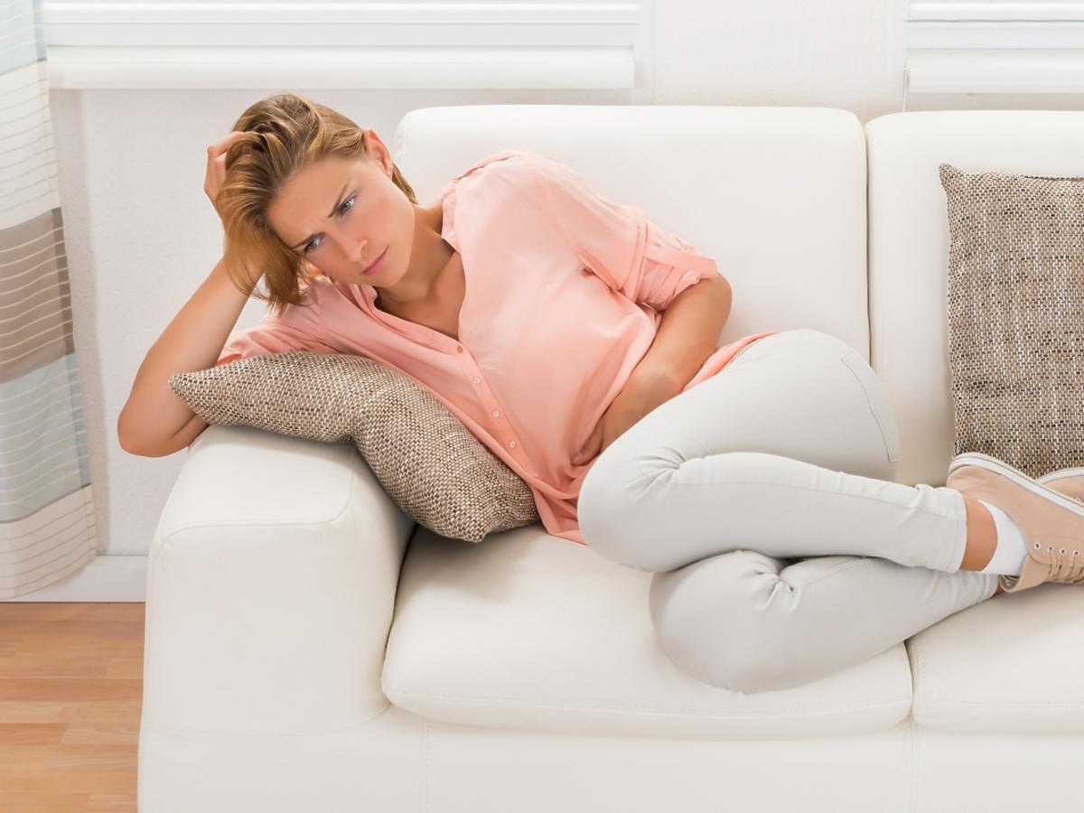 Zmartwiona kobieta leży na białej kanapie
