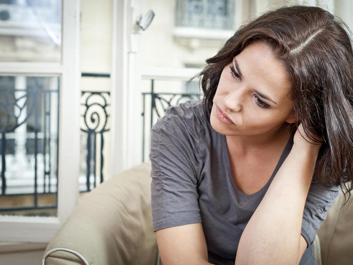 zmartwiona kobieta siedząca na kanapie