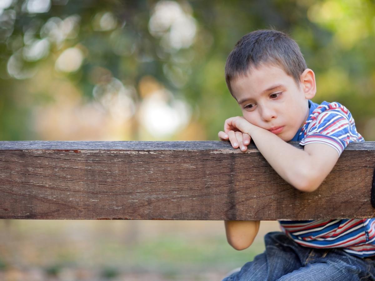 zmartwiony chłopczyk siedzi na ławce