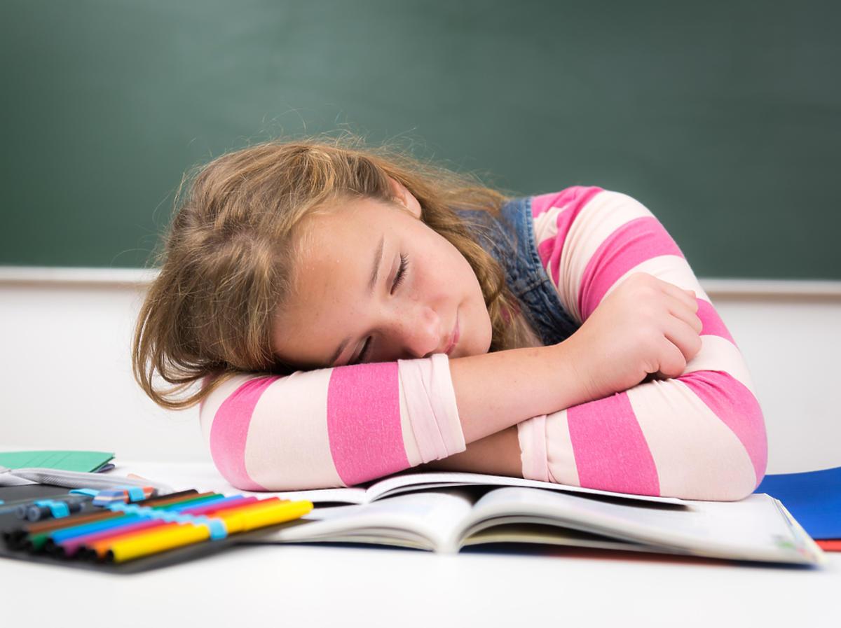 Zmęczona dziewczyna odpoczywa przy biurku