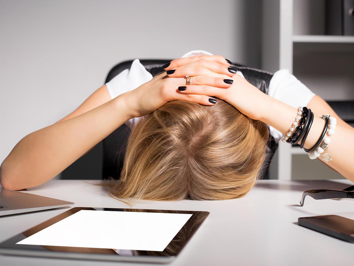 Zmęczona kobieta w pracy leży twarzą na biurku.