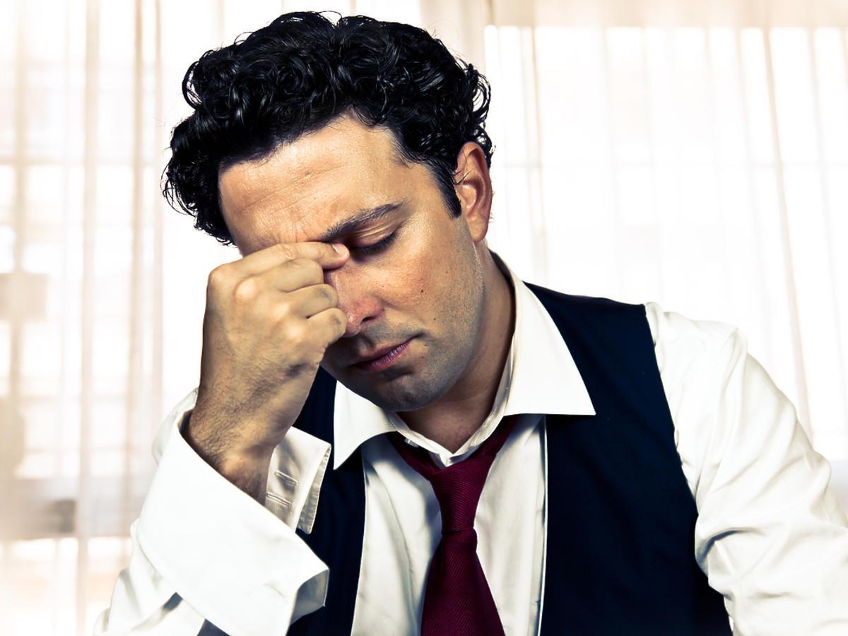 Zmęczony i zmartwiony mężczyzna podpiera ręką głowę
