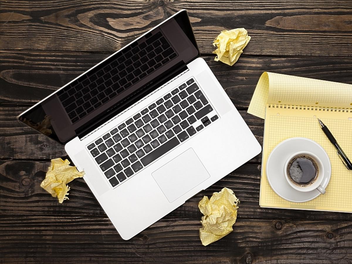 Zmięte kartki papieru, długopis i laptop.